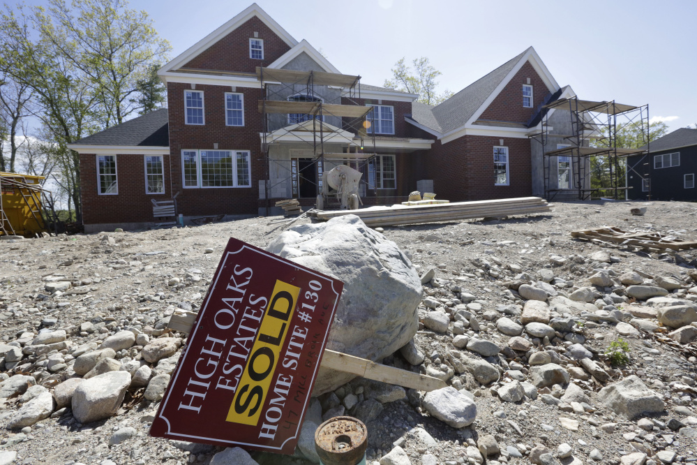 """A """"Sold"""" sign rests in front of a house under construction, in Walpole, Mass. The Commerce Department reports on sales of new homes dropped in May."""