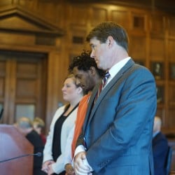 Abil Teshome is flanked by his attorneys, Alison Thompson and Jon Gale, at the Cumberland County Courthouse in Portland Thursday.