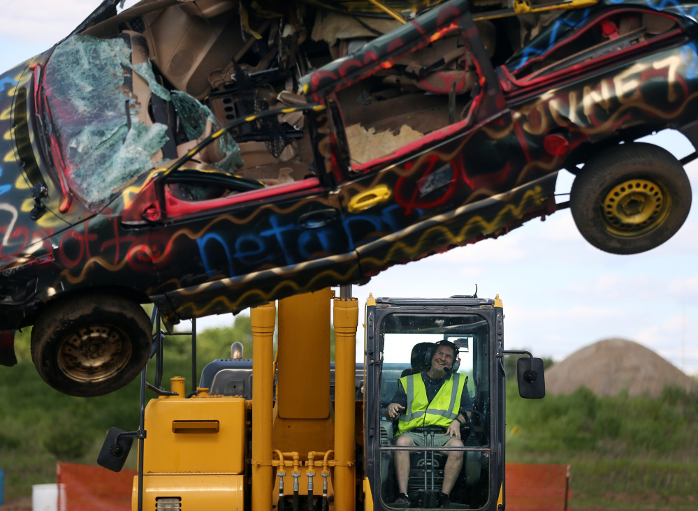 Mike Cossette uses an excavator to smash a minivan while taking part in a team-building event at Extreme Sandbox in Hastings, Minn. Extreme Sandbox offers a chance to operate full-size excavators, loaders and bulldozers on 10 acres of dirt and mud for those willing to pay hundreds of dollars for the experience.