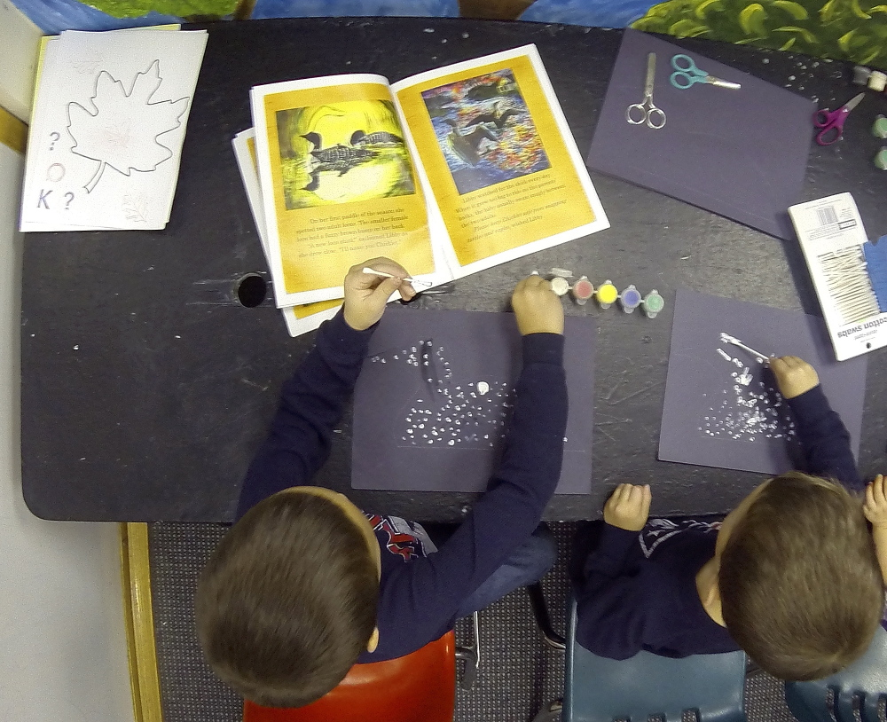 Keaton Gregoire, 6, left, and Isaac Gregoire, 4, both of Greene, do an art project after hearing Nancy Prince read her book