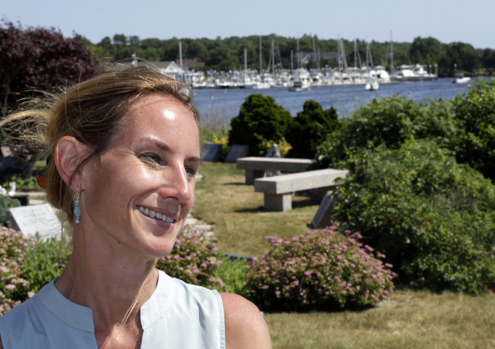 In this Monday, June 20, 2016 photo, Danielle Hetu speaks about the Westerly Yacht Club's membership policy as the yacht club is seen in the background in Westerly, R.I. Wives can join as associate, non-voting members, but unmarried women can't. A vote to change the nearly century-old policy failed last week, with 171 men voting to uphold it. Women, and many men, are not happy. (AP Photo/Elise Amendola)