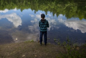 Andrew Mullin, 11, of Scarborough, drops a dragonfly lure in Otter Pond from the edge of Turtle Point in Sebago Lake Land Reserve. Mullin was fly-casting with his grandfather Peter Romano.