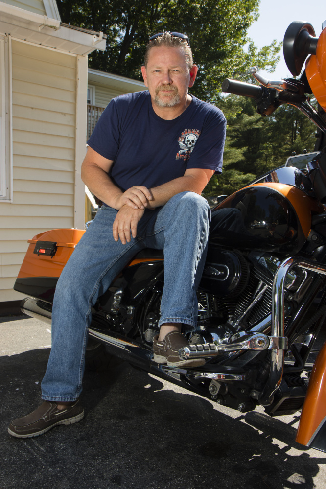 "Chuck Phillips, 49 sits on his motorcycle outside his house in Saco on Friday. He says he'll vote for Trump, but also has issues with the Republican. ""I'm not overly crazy about him but I find him the more palatable candidate."""