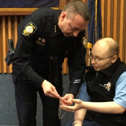 Portland Police Chief Michael Sauschuck hands Zachary Johnson a St. Christopher medal the chief had worn around his neck.