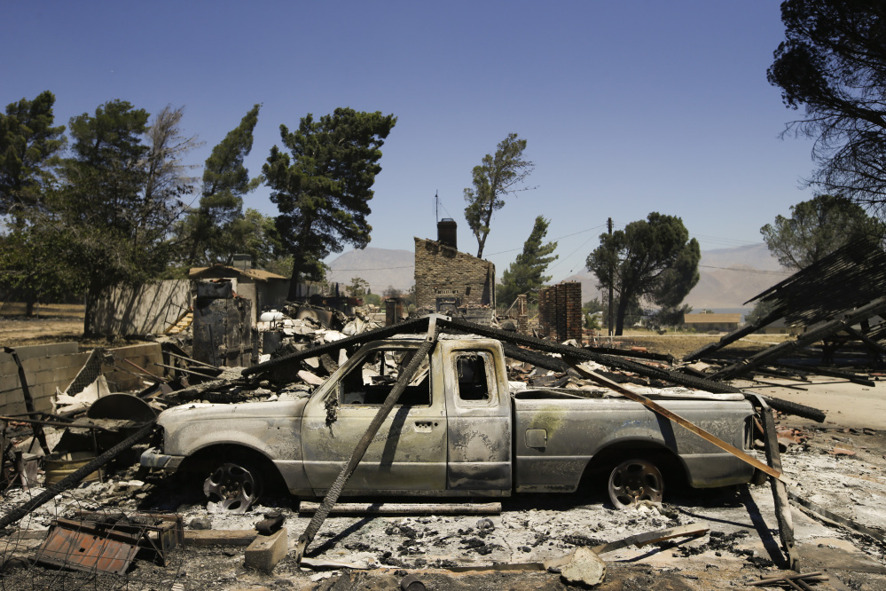 A pickup truck destroyed by fire sits on a burned-down property on Friday near Lake Isabella, Calif.