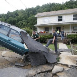 Jay Bennett, left, and stepson Easton Phillips survey the damage to a neighbor's car in front of their home, which was damaged by floodwaters, as the cleanup begins from severe flooding in White Sulphur Springs, W. Va., on Friday.