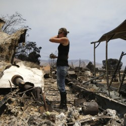 A distraught Amy Nelson goes through the remains of her South Lake, Calif., home Saturday that was devastated by a wildfire.