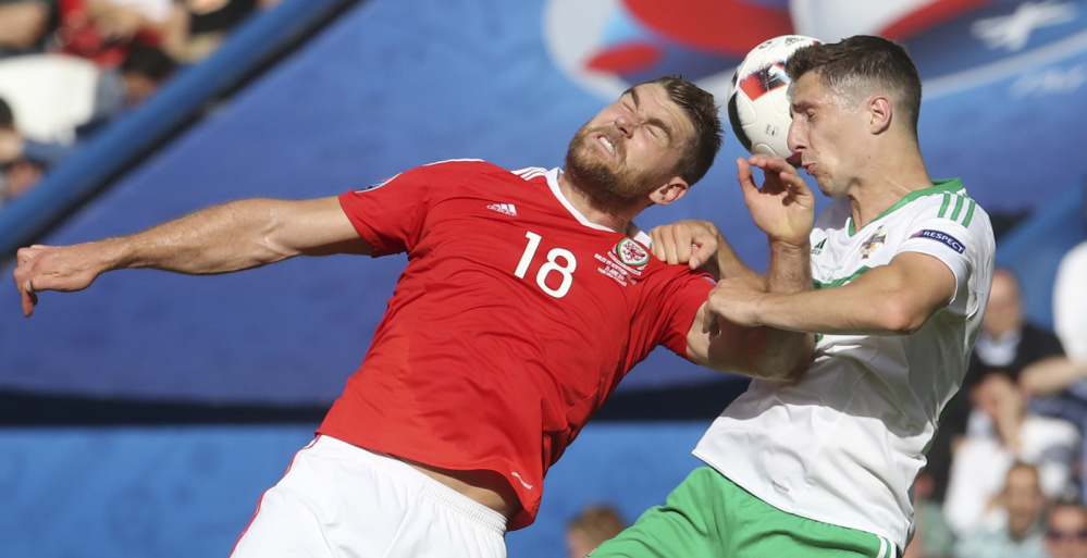 Sam Vokes, left, of Wales and Craig Cathcart of Northern Ireland challenge for the ball during their Round of 16 match Saturday in the European Championships in Paris. Wales, which qualified for a major tournament for the first time since the 1958 World Cup, won 1-0 and will meet Hungary or Belgium in a quarterfinal.