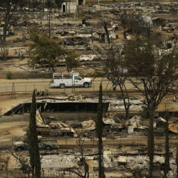 A pickup truck passes by the remains of mobile homes devastated by a wildfire, Saturday in South Lake, Calif.