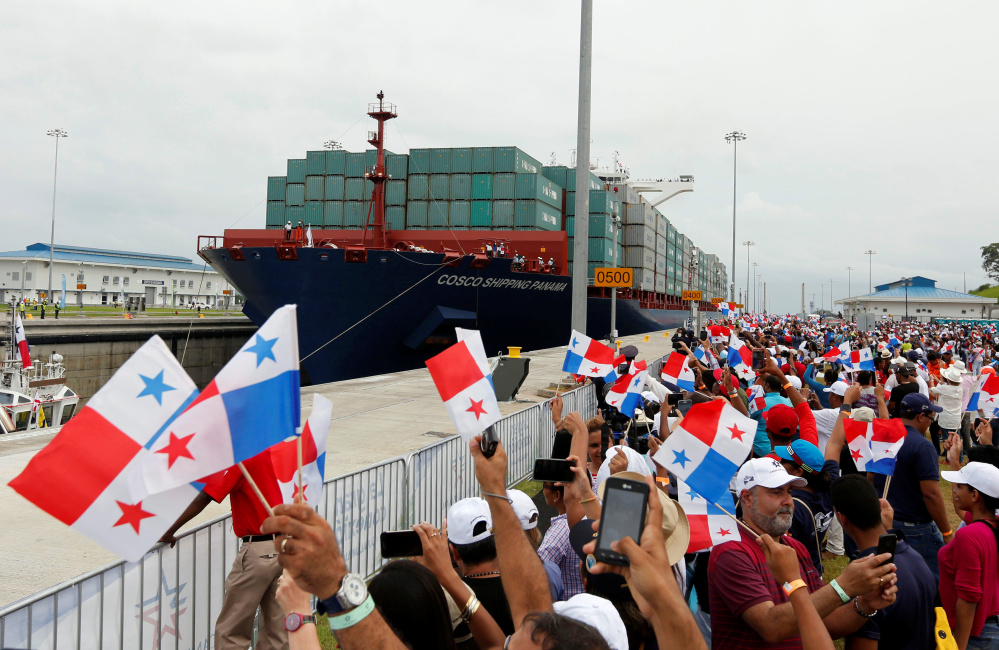 People wave Panamanian flags as a massive Chinese COSCO container vessel navigates through the Agua Clara locks during the first ceremonial pass through the Panama Canal on Sunday.