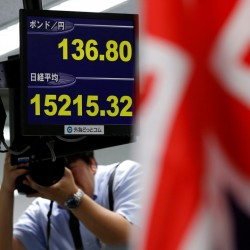 A photographer take photos of monitors displaying the yen's exchange rate against the British pound and Japan's Nikkei share average Monday at a trading company in Tokyo.