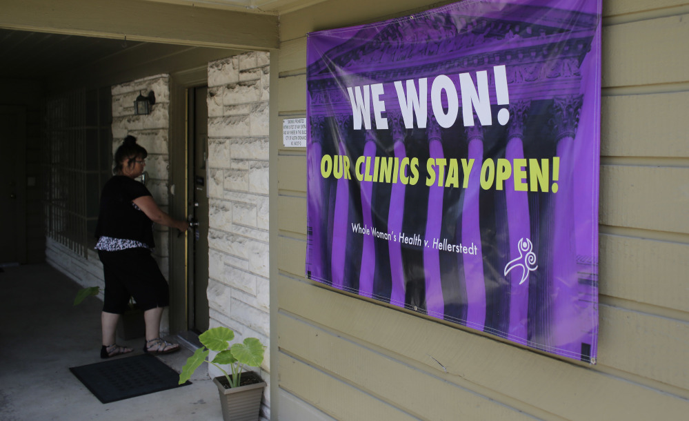 A poster put up Monday at the Choice Clinic, formerly Whole Woman's Health Clinic, in Austin, Texas, hails a historic ruling that strikes down one of the most restrictive state abortion laws in the U.S.