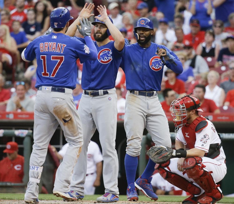 Kris Bryant, left, of the Chicago Cubs is greeted at the plate by teammates Jake Arrieta, center, and Jason Heyward after Bryant's three-run homer during an 11-8 win by the Cubs at Cincinnati on Monday. Bryant had three homers and two doubles in the game.