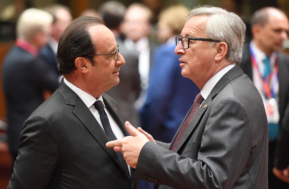 European Commission President Jean-Claude Juncker, right, speaks with French President Francois Hollande during a round table meeting at an EU summit in Brussels on Tuesday.