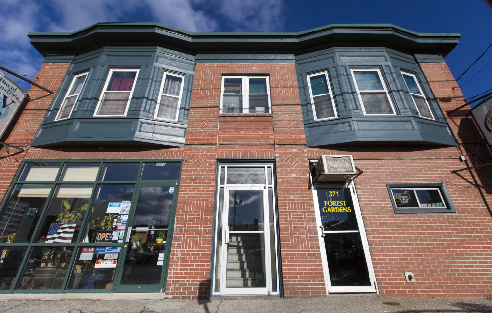 David Munster's TV store, left, and Forest Gardens share a building on Forest Avenue whose future depends on rezoning  and historic landmark status.   Ben McCanna/ Staff photographer