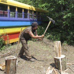 A member of the Rainbow Family of Living Light, who goes by the name of Joe, splits wood Tuesday at his campsite in Mount Tabor, Vt. Some locals have bemoaned the invasion of painted buses and visitors in torn clothes, body paint and dreadlocks.