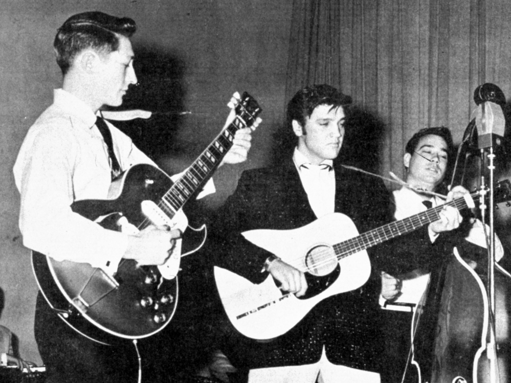 Elvis Presley performs on tour in the summer of 1957, with Scotty Moore on guitar, left, and Bill Black on the standup bass. Moore died at home in Nashville on Tuesday.