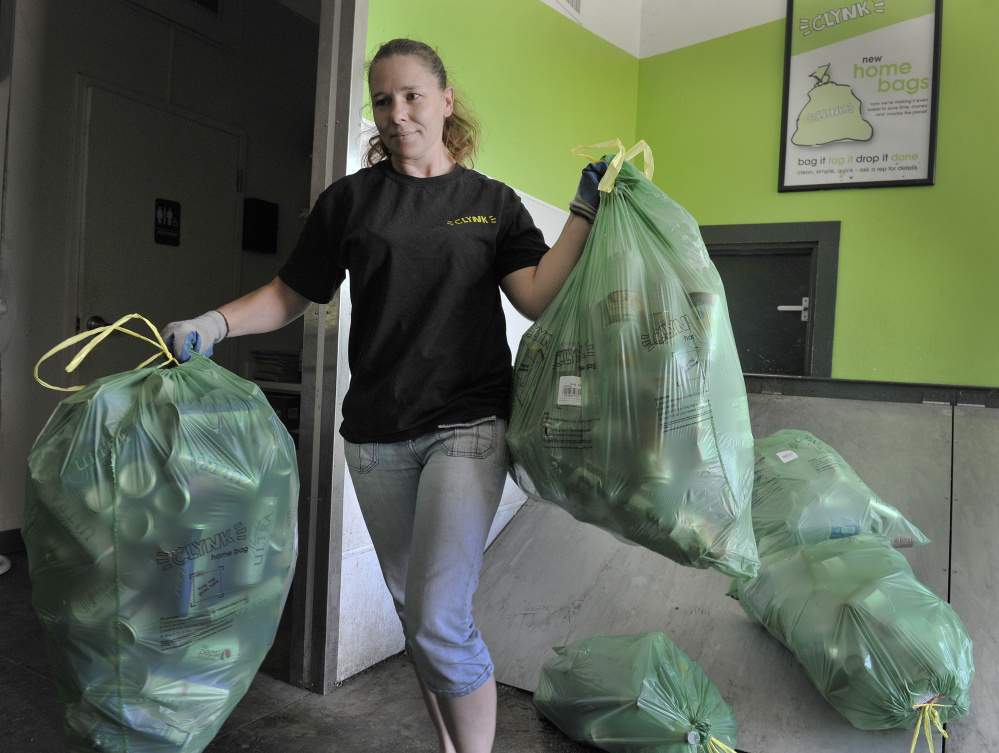 Longtime Clynk employee Loriann Day moves bags of bottles and cans at the company's redemption center at the Hannaford store in Scarborough on Monday.