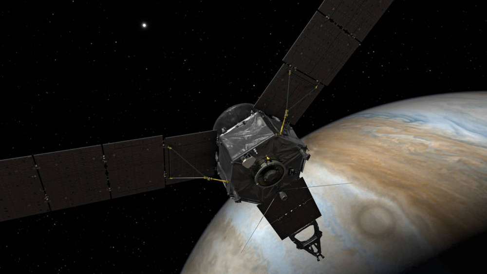 NASA's Juno spacecraft is shown above Jupiter, a planet so huge that more than 1,300 Earths could fit inside it.