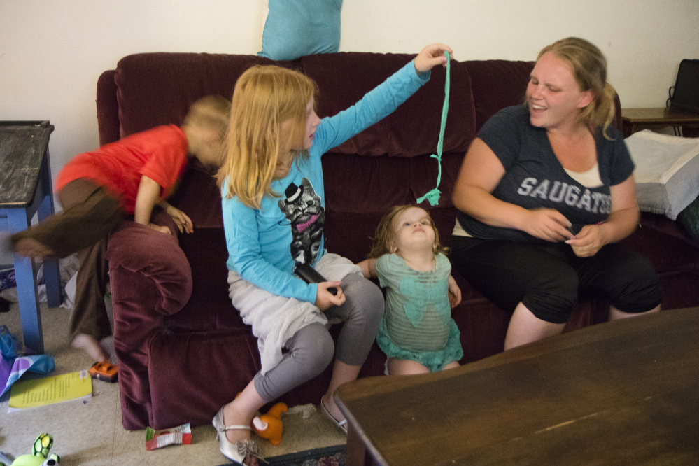 Sandra Vermette sits with her children in their apartment at Cranberry Ridge, a 16-unit subsidized complex in Sanford.