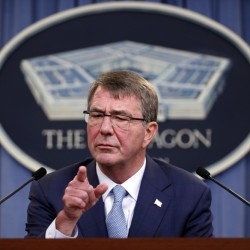 "Defense Secretary Ashton Carter takes a question at a news conference at the Pentagon on Thursday while announcing new rules allowing transgender people to serve openly in the U.S. military. ""Our mission is to defend this country,"" he said, ""and we don't want barriers unrelated to a person's qualification to serve."""