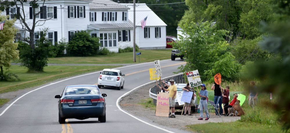 Demonstrators stand on Main Street in Vassalboro to oppose the planned removal of Masse Dam, which will drain Mill Pond, as part of an effort to restore alewife populations.