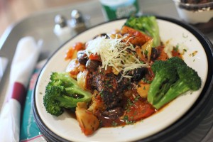 Mediterranean Chicken Saute is made with herb-coated chicken breast, artichokes, black olives and diced tomatoes, sauteed with white wine and served over risotto with broccoli on the side at Mercy Hospital.