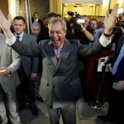 """Nigel Farage, the leader of the UK Independence Party, celebrates and poses for photographers as he leaves a """"Leave.EU"""" organization party Friday. """"Let June 23 go down in our history as our independence day!"""" he said. Associated Press"""