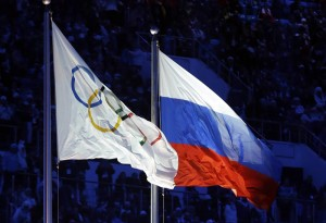 FILE - In this Feb. 7, 2014 file photo the Russian and the Olympic flags wave during the opening ceremony of the 2014 Winter Olympics in Sochi, Russia. The credibility of the fight against doping in sports will be at stake Friday, June 17, 2016 when track and field's world governing body decides whether to uphold or lift its ban on Russian athletes ahead of the Rio de Janeiro Olympics. Sports geopolitics — and the key issue of individual justice vs. collective punishment — frame the debate heading into the meeting of IAAF leaders in Vienna.  (AP Photo/Patrick Semansky, file)