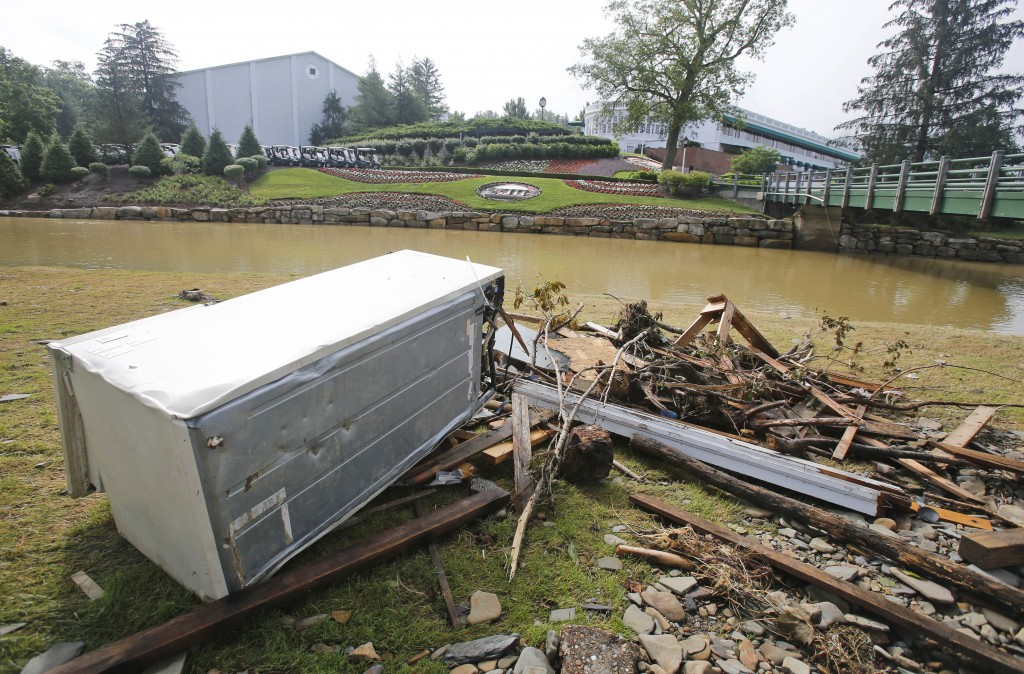 Debris is stacked up along Howard Creek in front of the first tee and the clubhouse as workers survey and begin the cleanup of the Old White Course on the property of the Greenbrier Resort in White Sulphur Springs, W. Va., Tuesday.    Associated Press Photo/Steve Helber