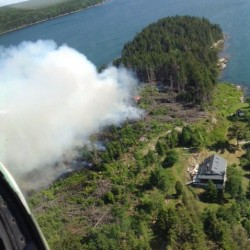 Smoke rises from a fire near a home on Sheep Island off Harpswell on Friday.