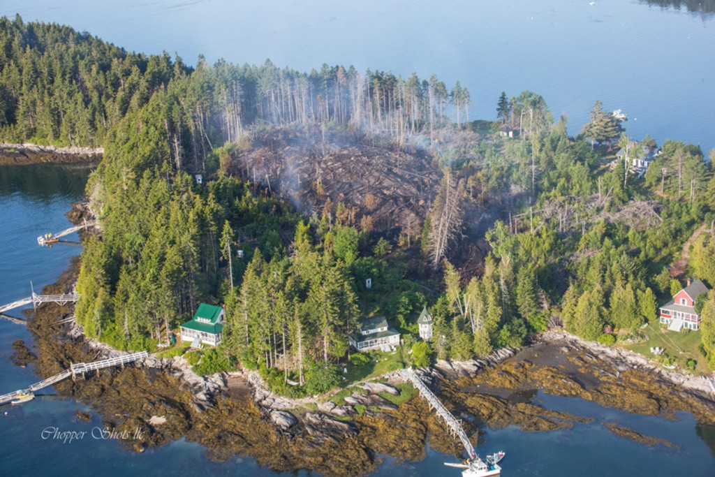 Cottages ring the area burned by fire Friday on Sheep Island in Casco Bay. Firefighters remained on the island Saturday morning to knock down hot spots.
