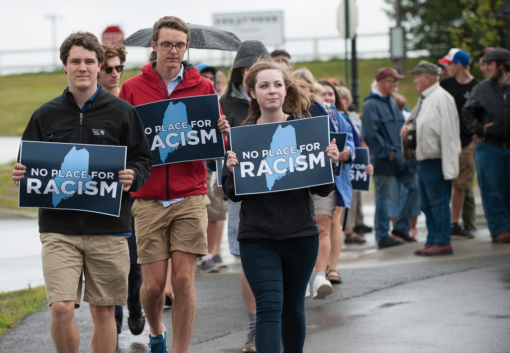 Protesters march past Donald Trump supporters as part of a demonstration organized by the Maine People's Alliance at the Cross Insurance Center in Bangor on Wednesday.
