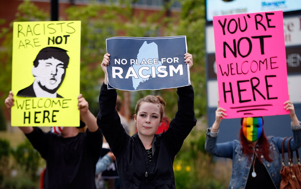 Meagan Cloutier, of Old Town, center, and others hold signs outside a rally for Republican presidential candidate Donald Trump on Wednesday in Bangor.