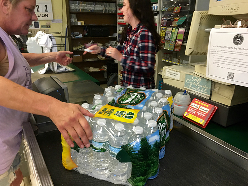 Hannigan's Island Market cashier Brook Tracy rings up a case of bottled water just minutes after opening at 8 a.m. Thursday. By 8:15, the small store was sold out.