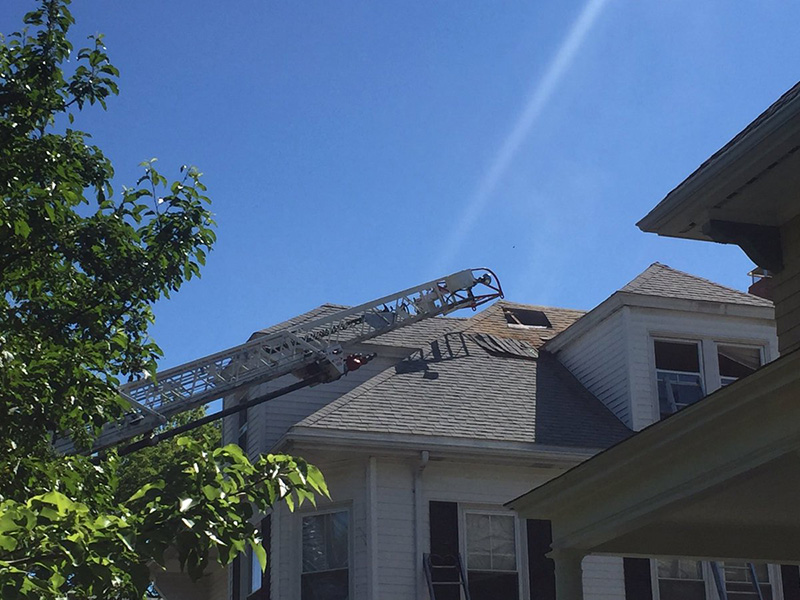 Portland firefighters cut a hole to vent the attic of the house 33 Clifton Street.