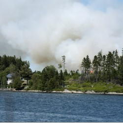 Smoke rises over Sheep Island inn Casco Bay, where about four acres burned Friday.