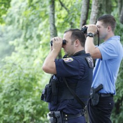 Officer Phil Robinson and Garrett McCarthy look out on to the river in Westbrook, Maine after a large snake was sighted eating an animal overnight.