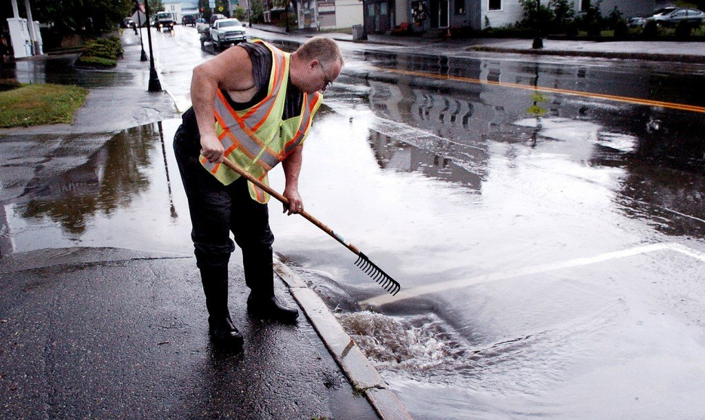 Madison Public Woks employee Bill Pierce clears a drain after a strong storm flooded Main Street on Monday afternoon.