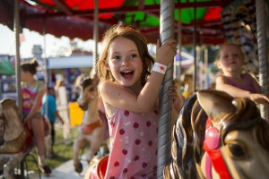Naomi Peterson, 5, of Portland rides on the carousel at the carnival of the 51st annual Clam Festival parade in Yarmouth on Friday. Brianna Soukup/Staff Photographer