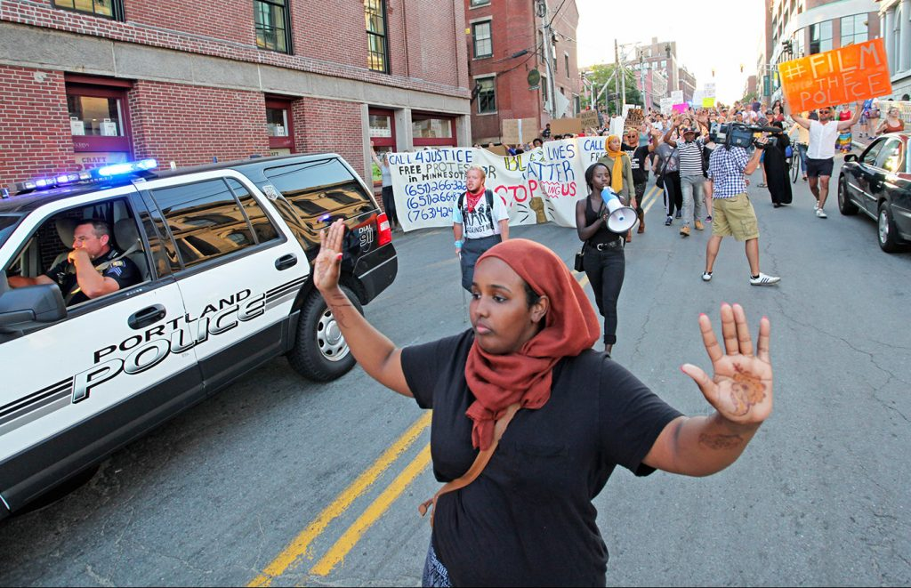 "Shadiyo Hussain chants, ""Hands up, don't shoot!"" with about 150 people as they march from Lincoln Park down Pearl Street to Commercial Street for a Black Lives Matter protest on July 15, 2016. The arrests made soon after began a court case that now appears to be over."