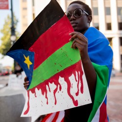 PORTLAND, ME - JULY 22:  Lucy Otto, 16, of Portland, wears the South Sudanese flag and holds up a poster of the flag dripping with blood at at Monument Square while at a rally for awareness about the situation in South Sudan. Otto was born in South Sudan came to the United States when she was five years old. (Photo by Brianna Soukup/Staff Photographer)