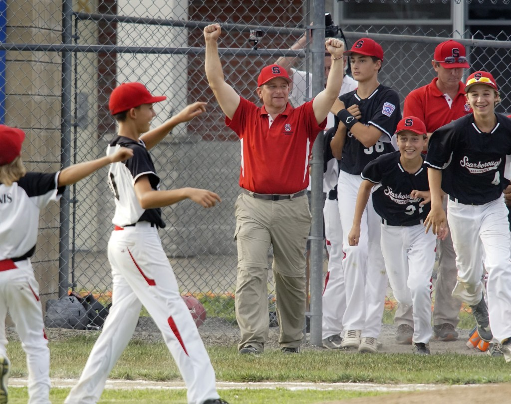 Scarborough Coach Pat Donahue and players Ryan Gambardella, 4, and Sam Rumelhaut run onto the field after the final out in the fourth inning of the Little League state championship game in Orrington on Friday. Photo by Michael C. York.