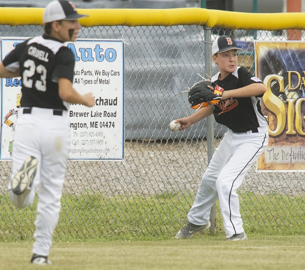 Biddeford's Ashton Crowell, left, and Caleb Vigue chase down a ball up against the fence in the fourth inning. Photo by Michael C. York