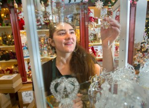 Tori Broshes, 19, a sales associate at Christmas Noel, a holiday ornament shop on Exchange Street in Portland, looks at a display of tiny crystal Christmas ornaments.