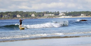 A paddleboarder catches a wave at Higgins Beach in Scarborough.
