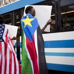 Joyce Augustino, 15, left, and Lucy Otto, 16, both of Portland, wear the American and South Sudanese flags and hold up signs at at Monument Square during a rally to raise awareness about the situation in South Sudan. Both Augustino and Otto came to the United States as young children.