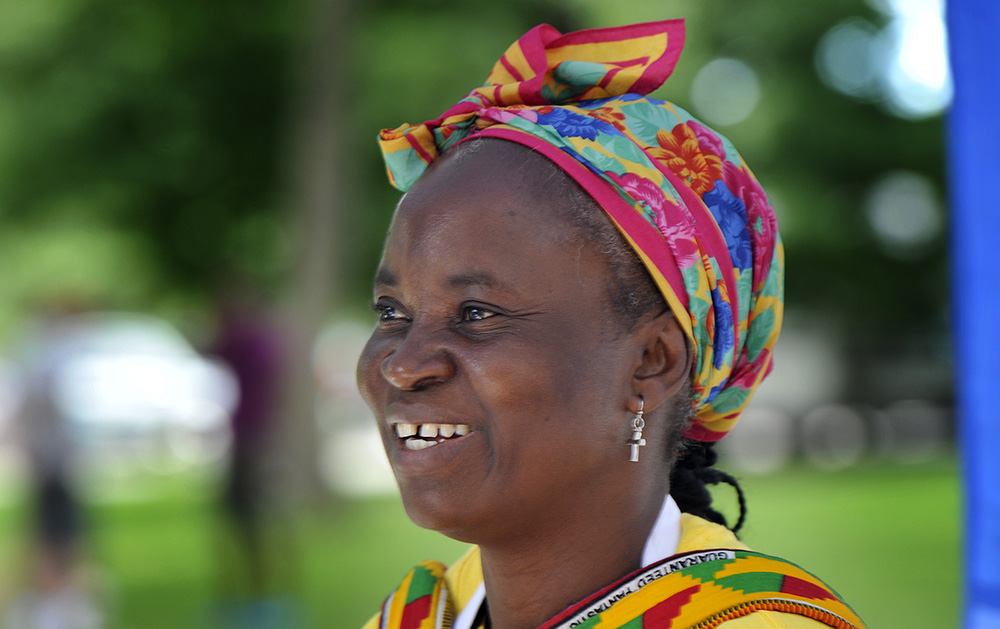 Kadiatu Moriba of Portland, who grew up in Sierra Leone, smiles as she talks with visitors to her food stand where she was serving African foods at the Festival of Nations Saturday. Shawn Patrick Ouellette/Staff Photographer