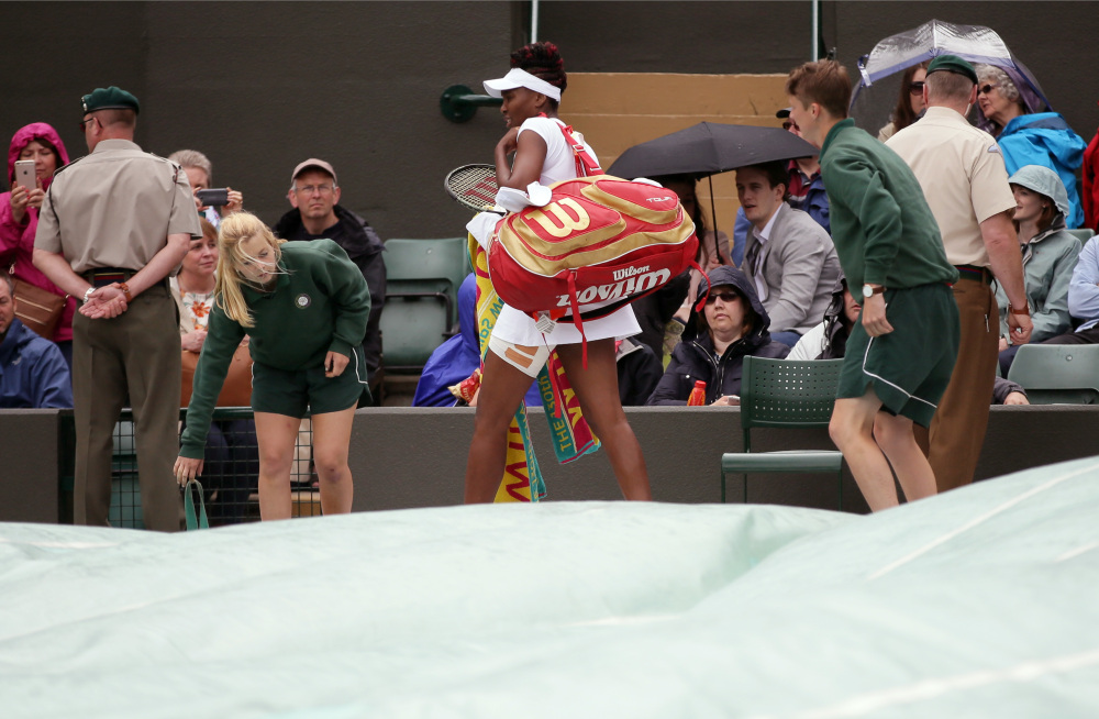 Venus Williams of the U.S leaves the court after rain delayed her women's singles match against Daria Kasatkina of Russia on day five of the Wimbledon Tennis Championships in London Friday, July 1, 2016. (AP Photo/Tim Ireland)
