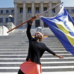 Katherine Day waves the Human Rights Campaign flag at the Mississippi Capitol in Jackson, Miss., on Friday. Gov. Phil Bryant will appeal a recent federal ruling upholding gay marriage.